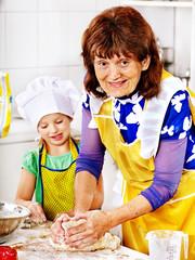 Grandmother and grandchild baking cookies.