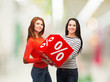 two smiling teenage girl with percent sign on box