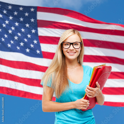 smiling student in eyeglasses with folders - 60253885