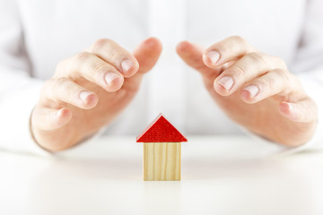 Male hands covering and protecting a home