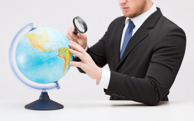 businessman hand holding magnifier over globe