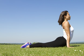 Young woman outdoors in a yoga cobra pose - bhujangasana