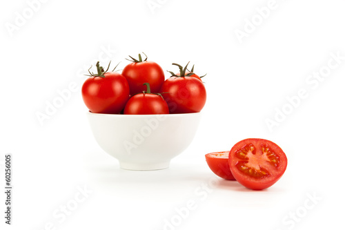 white bowl of red tomatoes on a white background