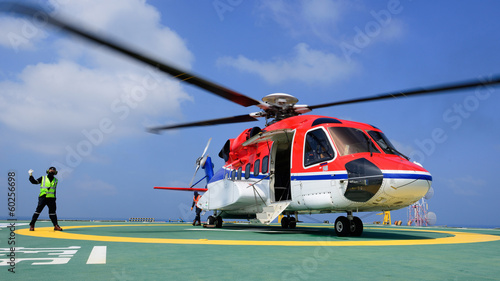 canvas print picture The helicopter landing officer give signal to passenger to embar