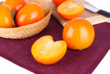 Ripe persimmons in wicker basket on table close-up