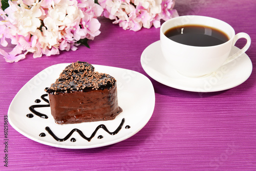 Sweet cake with chocolate on plate on table close-up