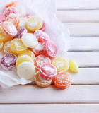 Sweet  multicolor candies on paper, on  color wooden background