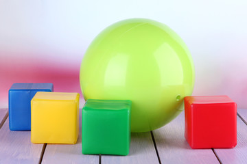 Bright ball and colorful  cubes on table on bright background