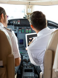 Pilot And Copilot Using Digital Tablet In Cockpit