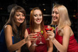 three girls raised their glasses in a nightclub