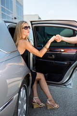 Man's Hand Helping Woman Stepping Out Of Car