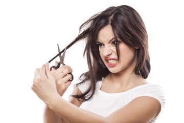 angry girl cuts her hair with scissors