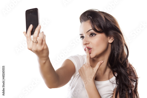 girl make a selfies and kiss her finger
