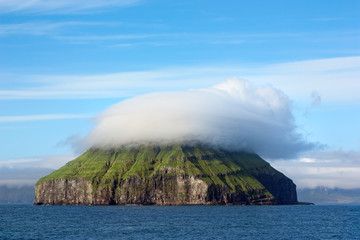 Remote rocky island covered by a curious cloud