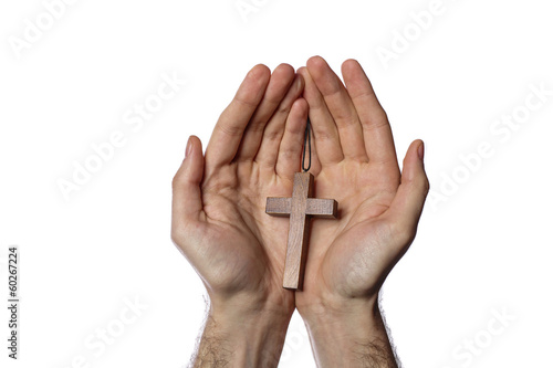 Male hands holding wooden cross on white background