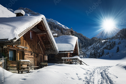 Fototapeta winter ski chalet and cabin in snow mountain landscape in tyrol