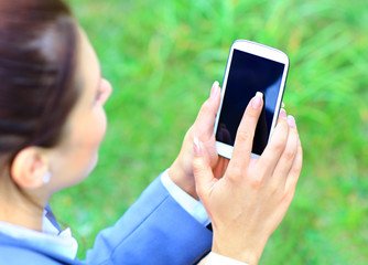 Woman hand holding smartphone against spring