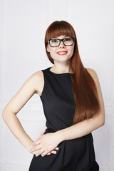 Woman with red hair in black glasses