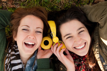 Happy teen girls sharing music