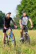 Young Couple With Bicycle In Meadow