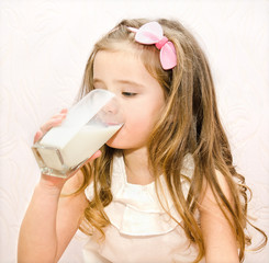 Beautiful little girl drinking milk