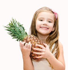 Happy little girl holding ripe whole pineapple