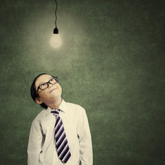 Smart little businessman looking at lit bulb