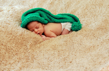 newborn baby is wearing a blue hat and laying down sleeping
