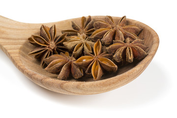 star anise in a wooden spoon isolated on white