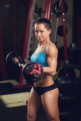 Healthy girl lifting bar with weights in the gym