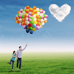 Cute couple flying with balloon