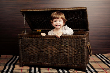 beautiful little girl sitting in suitcase