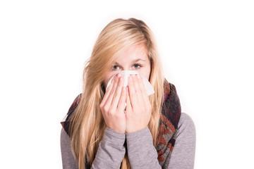Junge Frau ist erkältet und muss sich die Nase putzen