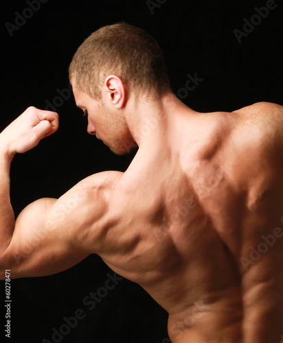 a young and fit male model posing his muscles.