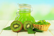 Jar of jam kiwi on wooden table on natural background
