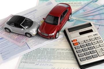Два автомобиля, калькулятор на фоне полиса, извещения и денег