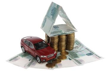 Дом из монет и автомобиль на купюрах и белом фоне
