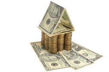 Дом из монет на долларах и белом фоне