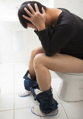 young man with frustrated expression sitting toilet seat