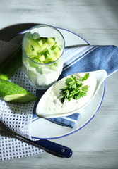 Cucumber yogurt in glass, on color napkin, on wooden