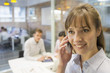 Portrait of smiling businesswoman on mobile phone in meeting