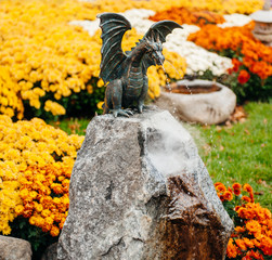 Statue of a dragon in garden surrounded by vibrant color flowers