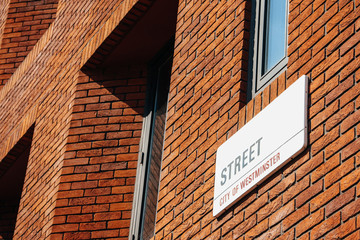 London typical streets sign on a red brick wall. Copy Space
