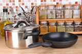 Pot and pan in kitchen on table on mosaic tiles background