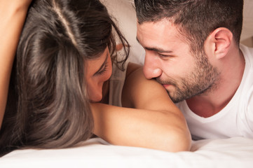Happy young couple playing in hotel room while laying on bed in