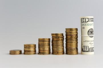 Пять стопок монет и сверток долларов на сером фоне