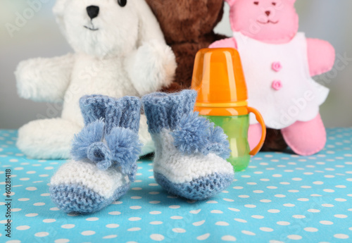 Composition with crocheted booties for baby, bottle, toy and