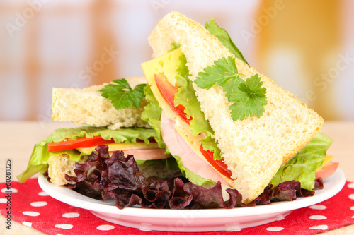 Fresh and tasty sandwiches on plate on table on light