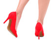 Beautiful female legs in red shoes isolated on white