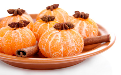 Ripe sweet tangerines on color plate, isolated on white